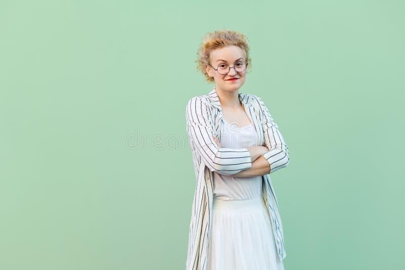 Portrait de jeune femme blonde heureuse dans la chemise blanche, la jupe, et le chemisier rayé avec des lunettes se tenant, des b photo stock