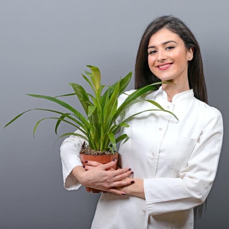 Portrait de jeune femme de botaniste à l'usine de participation d'uniforme sur le fond gris photo libre de droits