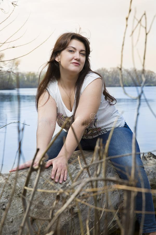 Portrait de jeune femme de brune en parc Belle pose modèle près de l'eau Modèle plus la taille photo stock