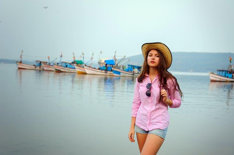 Portrait de jeune femme caucasienne dans le chapeau de paille et de shorts courts de denim un jour nuageux chaud Belle brune aux  photographie stock