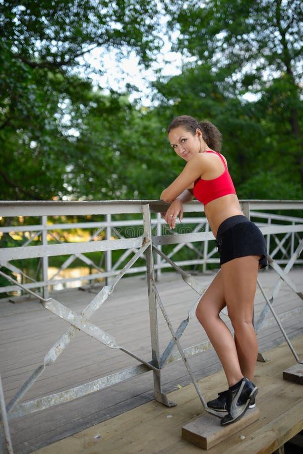 Portrait de jeune femme décontractée de forme physique sur le pont en bois en parc photos libres de droits