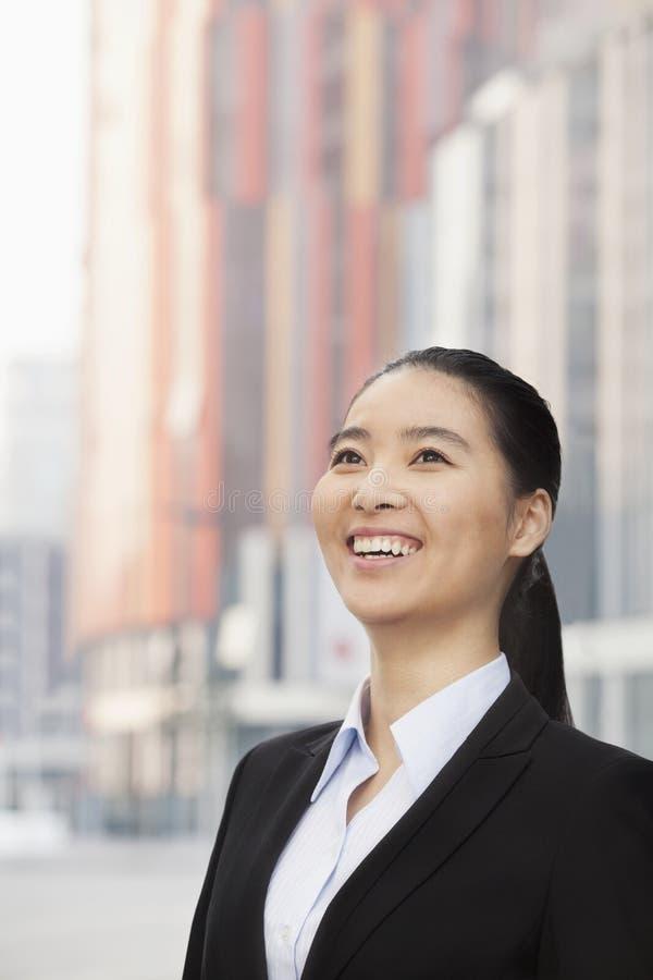 Portrait de jeune femme d'affaires de sourire avec une queue de cheval recherchant dehors avec des gratte-ciel à l'arrière-plan, P photo stock