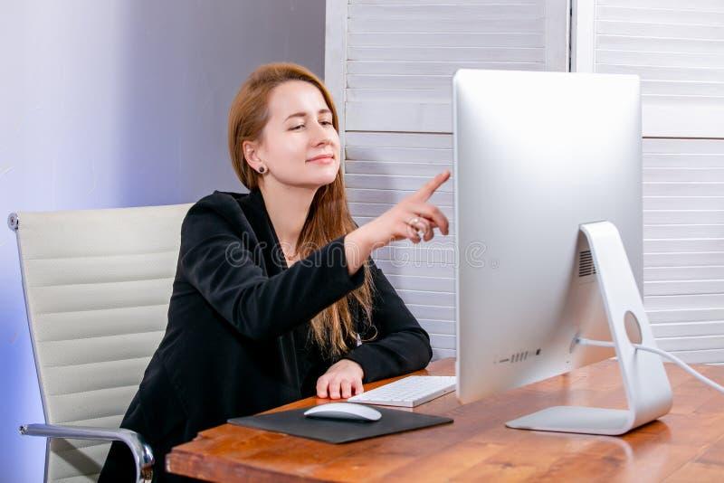 Portrait de jeune femme d'affaires réussie heureuse au bureau Elle s'assied à la table et aux points à l'affichage Black Friday o photo stock