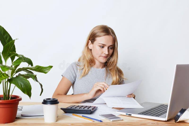 Portrait de jeune femme d'affaires travaillant avec l'ordinateur portable et la calculatrice, regardant attentivement des documen image stock