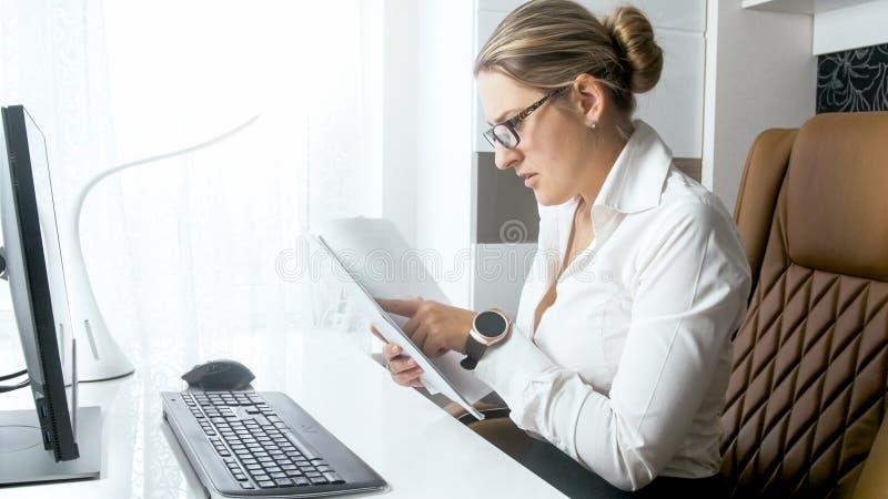Portrait de jeune femme d'affaires vérifiant l'information dans les documents photo libre de droits
