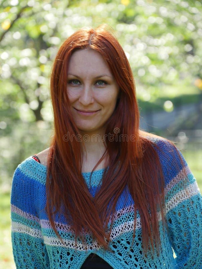 Portrait de jeune femme d'une chevelure rouge mignonne dans le chandail tricoté, extérieur photo libre de droits
