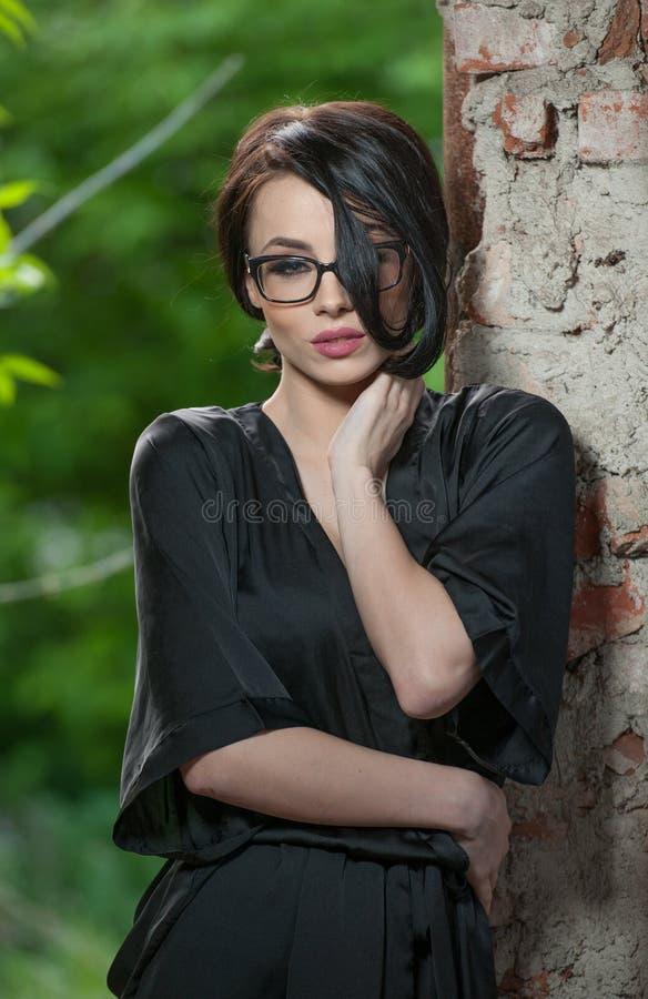 Portrait de jeune femme dans la robe de chambre en soie noire, se penchant contre le mur Belle femme aux cheveux courts séduisant photos libres de droits