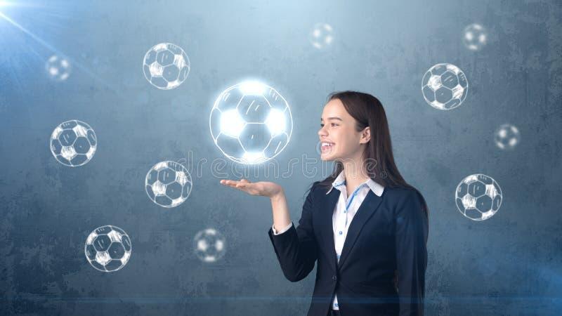 Portrait de jeune femme dans le costume tenant le ballon de football sur la paume ouverte de main, fond dessiné de studio Concept photos stock