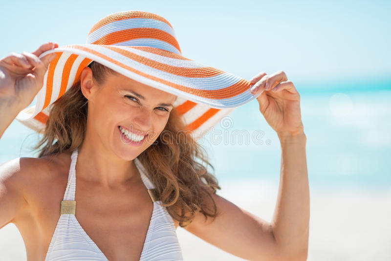 Portrait de jeune femme de sourire dans le chapeau sur la plage photographie stock