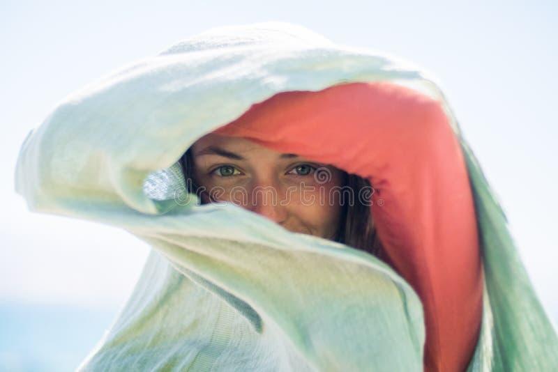Portrait de jeune femme de sourire heureuse avec de longs cheveux Elle cache et crée une ombre avec l'écharpe photographie stock