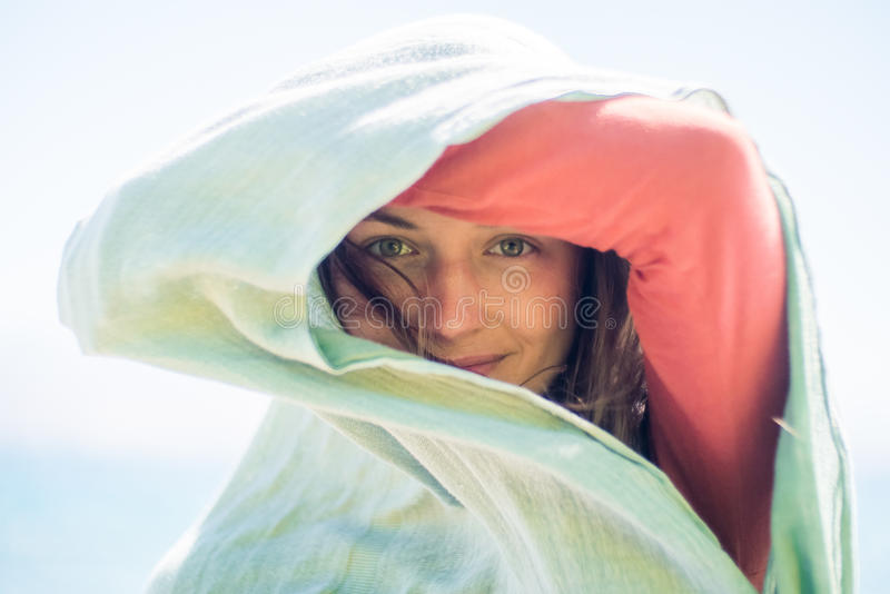 Portrait de jeune femme de sourire heureuse avec de longs cheveux Elle cache et crée une ombre avec l'écharpe image stock
