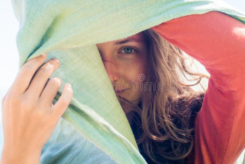 Portrait de jeune femme de sourire heureuse avec de longs cheveux Elle cache et crée une ombre avec l'écharpe images stock