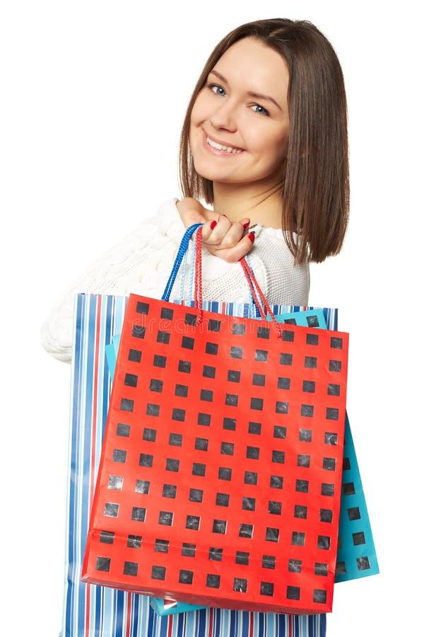 Portrait de jeune femme de sourire heureuse avec des sacs à provisions, d'isolement au-dessus du fond blanc image libre de droits