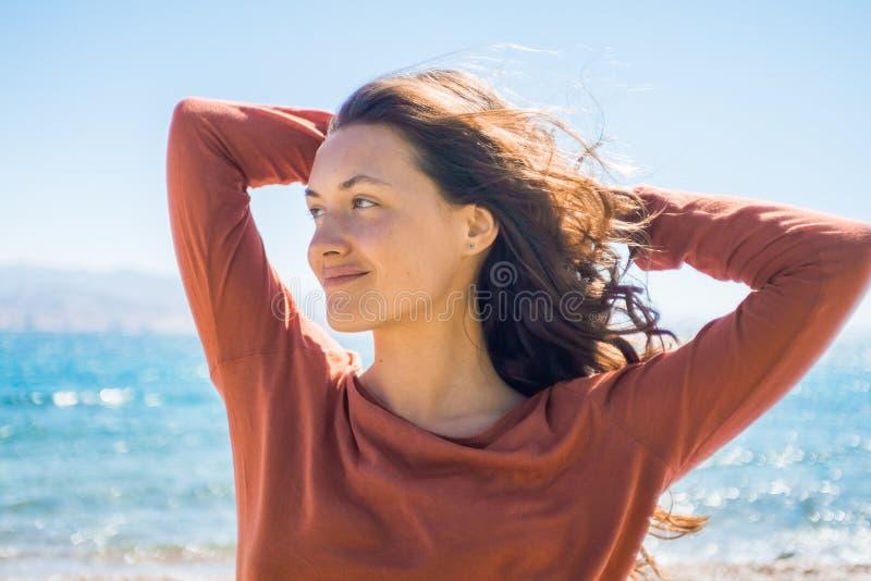 Portrait de jeune femme de sourire heureuse sur le fond de plage et de mer Jeux de vent avec de longs cheveux de fille images stock