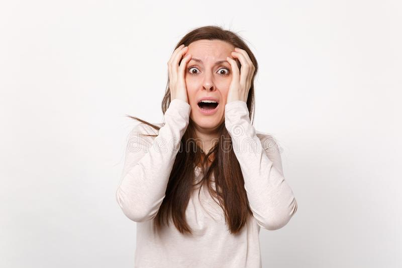 Portrait de jeune femme effrayée choquée dans des vêtements légers gardant les mains de mise grandes ouvertes de bouche sur le vi photographie stock