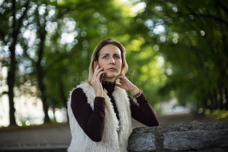 Portrait de jeune femme en été La fille blonde lit le message au téléphone portable dehors en nature de ville Femelle avec le tél photographie stock