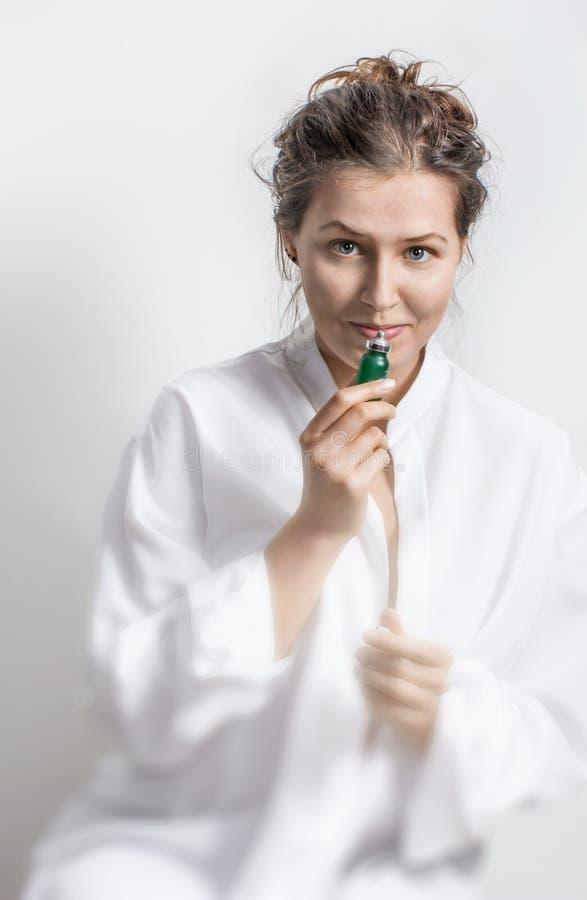 Portrait de jeune femme en tissu blanc avec le petit bot vert d'huile images libres de droits