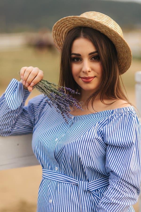 Portrait de jeune femme enceinte pr?s de la ferme Vue haute ?troite de dame dans le chapeau avec la lavande ? disposition Sourire image stock