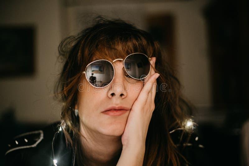Portrait de jeune femme ennuyée avec les lumières et les lunettes de soleil menées image stock