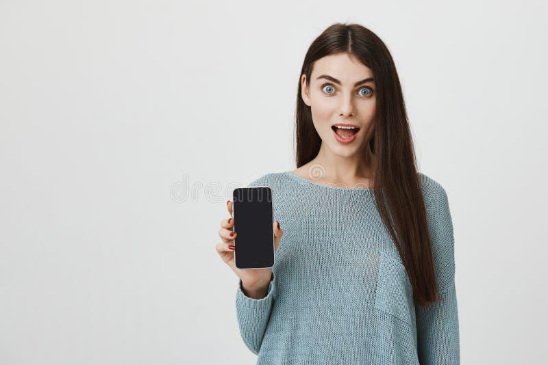 Portrait de jeune femme enthousiaste de brune avec les yeux sautés montrant l'écran de téléphone dans le choc avec la participati photos libres de droits