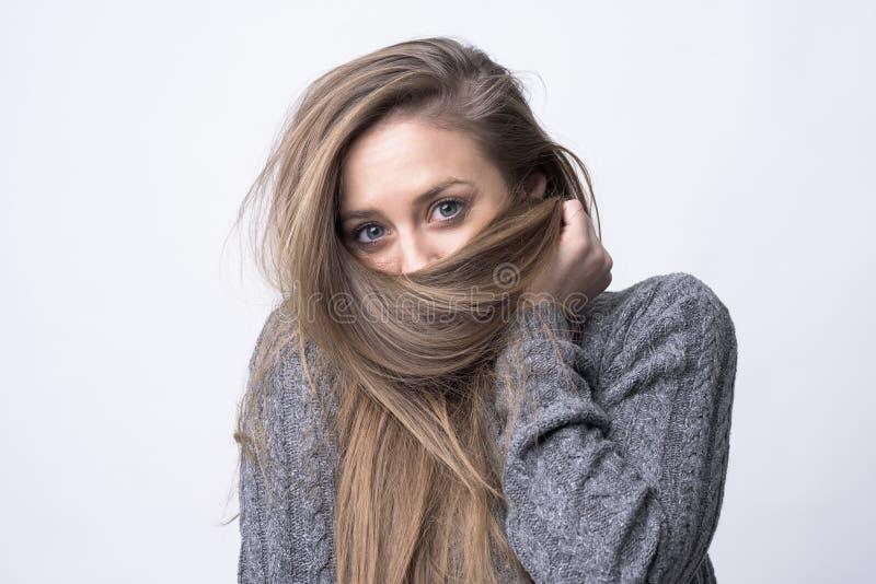 Portrait de jeune femme espiègle tenant de longs cheveux comme écharpe se cachant et couvrant photo stock