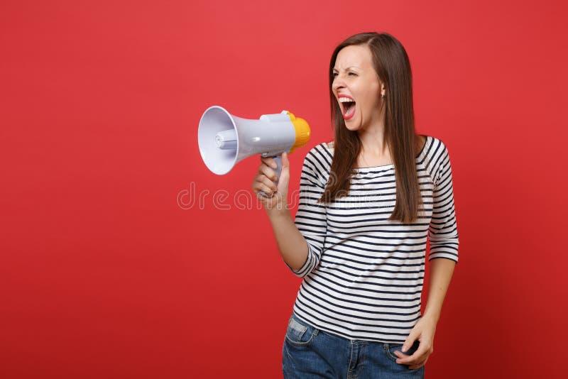 Portrait de jeune femme fâchée irritée dans des vêtements rayés regardant de côté, criant sur le mégaphone d'isolement sur le rou photos stock