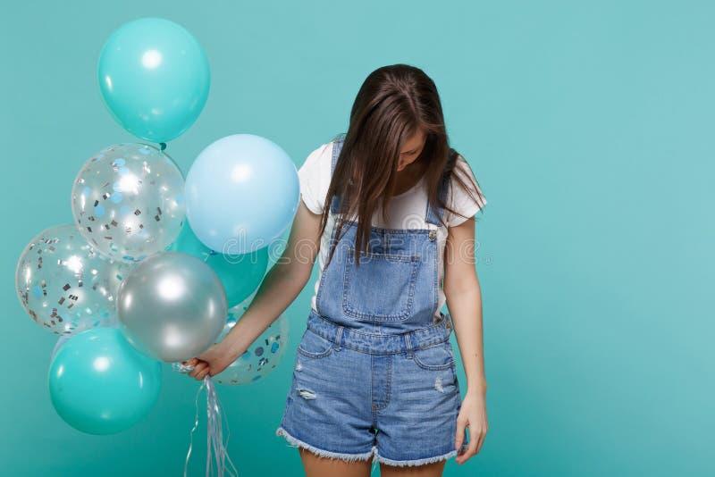 Portrait de jeune femme fatiguée dans des vêtements de denim avec le chef abaissé célébrant, jugeant les ballons à air colorés d' photographie stock