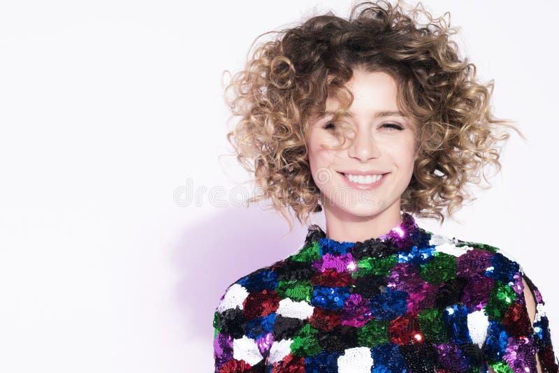 Portrait de jeune femme gaie avec un beau sourire devant un mur blanc images stock