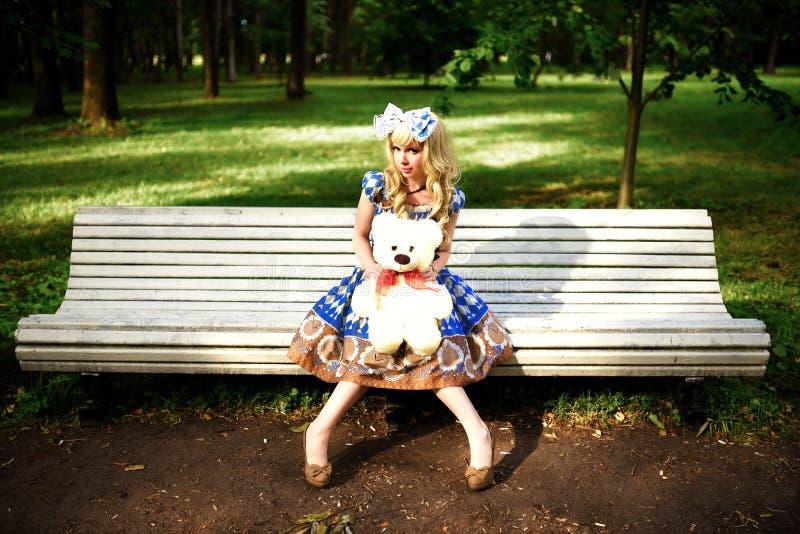 Portrait de jeune femme habillé comme poupée se reposant sur le banc image stock