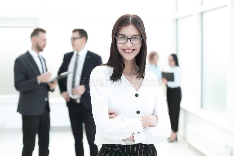 Portrait de jeune femme heureuse d'affaires au-dessus de fond de bureau image libre de droits