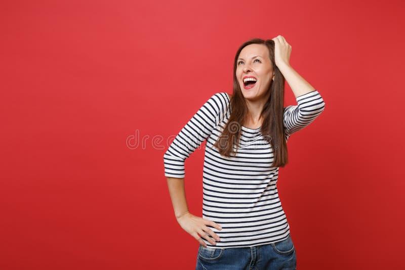 Portrait de jeune femme joyeuse dans la position rayée de vêtements, recherchant, mettant la main sur la tête d'isolement sur le  images libres de droits