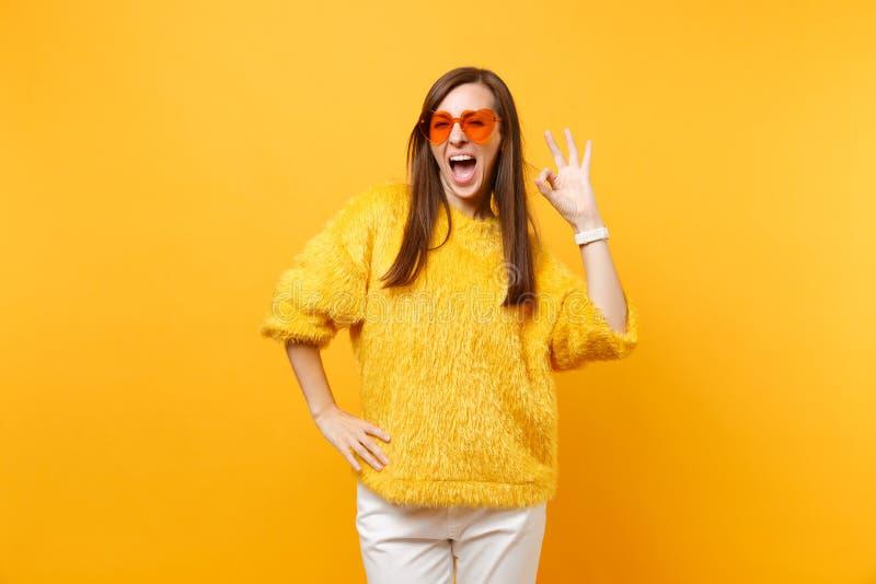 Portrait de jeune femme joyeuse en chandail de fourrure, pantalon blanc et verres oranges de coeur montrant le signe d'OK d'isole photo libre de droits