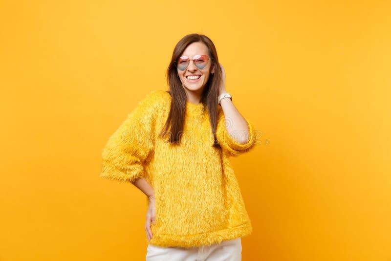 Portrait de jeune femme joyeuse de sourire dans le chandail de fourrure, verres de coeur mettant la main sur la tête d'isolement  photographie stock libre de droits