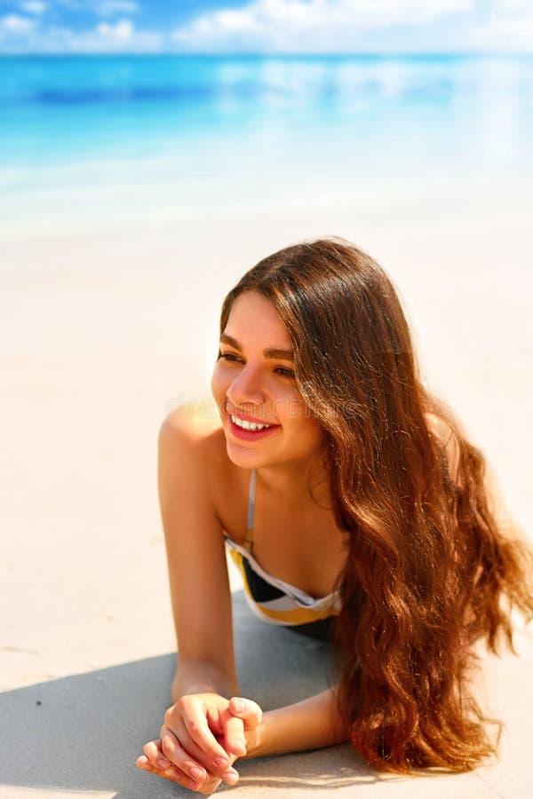 Portrait de jeune femme magnifique souriant tout en détendant sur la plage image libre de droits
