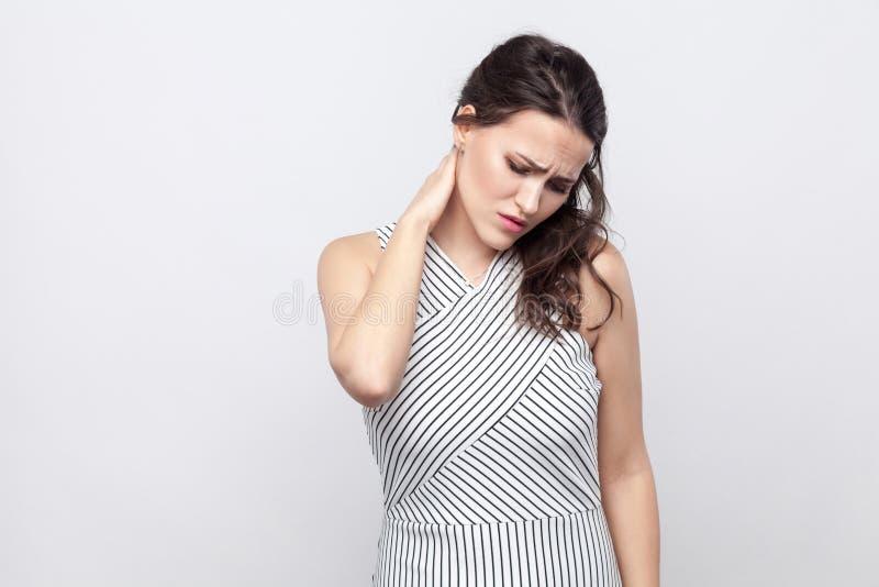 Portrait de jeune femme malade de brune avec le maquillage et la position rayée de robe tenant son cou et sentant la douleur photos libres de droits