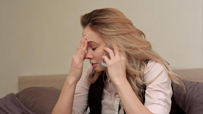 Portrait de jeune femme malheureuse faisant l'appel téléphonique contrarié à la maison photos stock