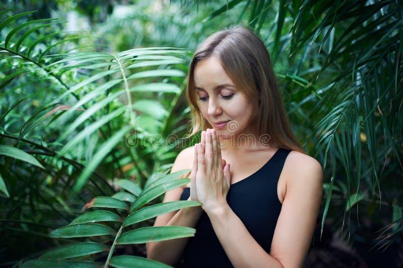 Portrait de jeune femme mignonne méditant et faisant la main de namaste dans la jungle Jour ensoleillé image stock