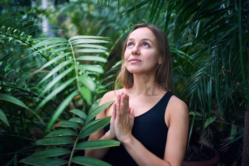 Portrait de jeune femme mignonne méditant et faisant la main de namaste dans la jungle Jour ensoleillé images stock