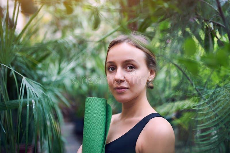 Portrait de jeune femme mignonne tenant un tapis roulé de yoga dans la jungle Jour ensoleillé images stock