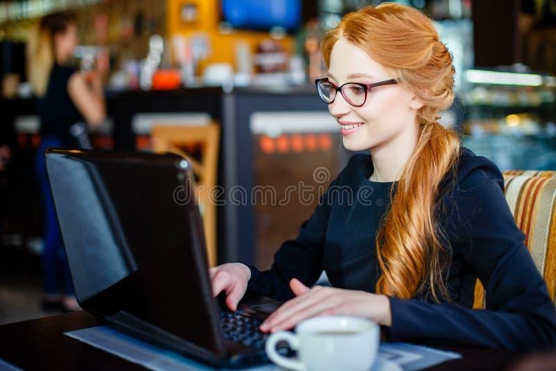 Portrait de jeune femme réussie avec l'ordinateur portable en café photos stock