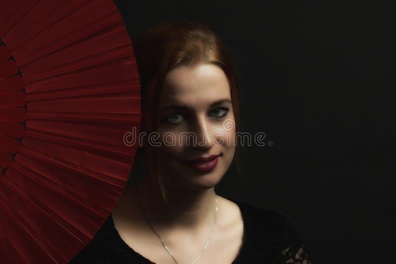 Portrait de jeune femme séduisante tenant la fan rouge photo stock