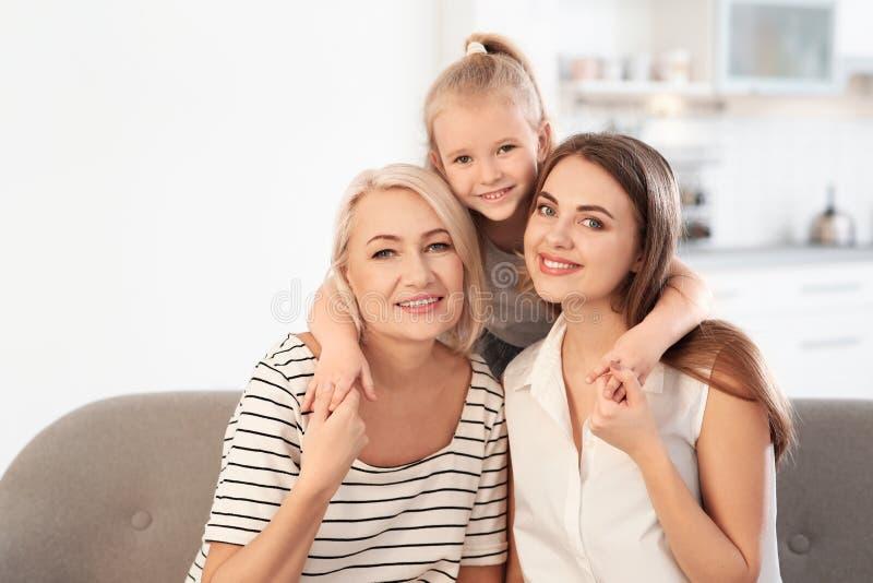 Portrait de jeune femme, de sa mère mûre et de fille sur le sofa image stock