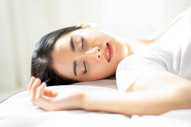 Portrait de jeune femme se trouvant au-dessus du backgroung blanc dans le lit à ho photographie stock
