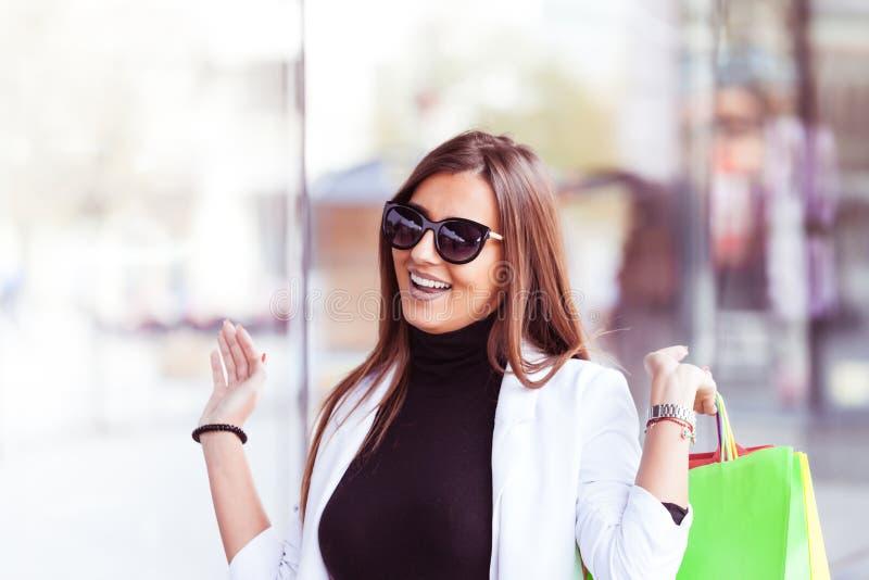 Portrait de jeune femme shopaholic avec l'abondance des paniers image stock