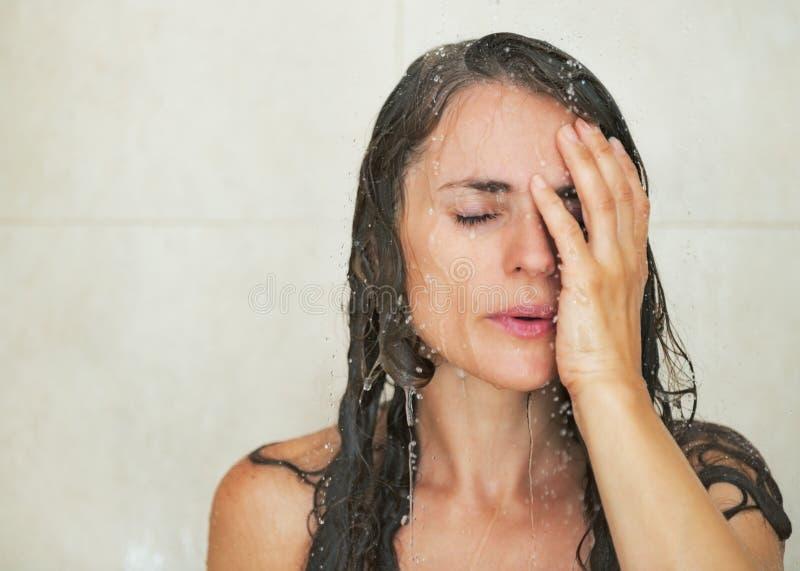 Portrait de jeune femme soumise à une contrainte dans la douche photo stock