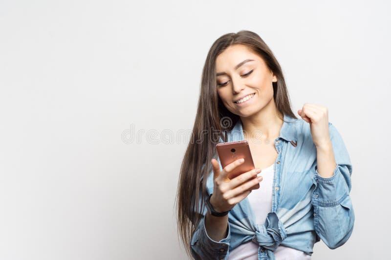 Portrait de jeune femme de sourire avec le smartphone rose recevant quelques grandes actualités au-dessus du fond blanc Mode de v photographie stock