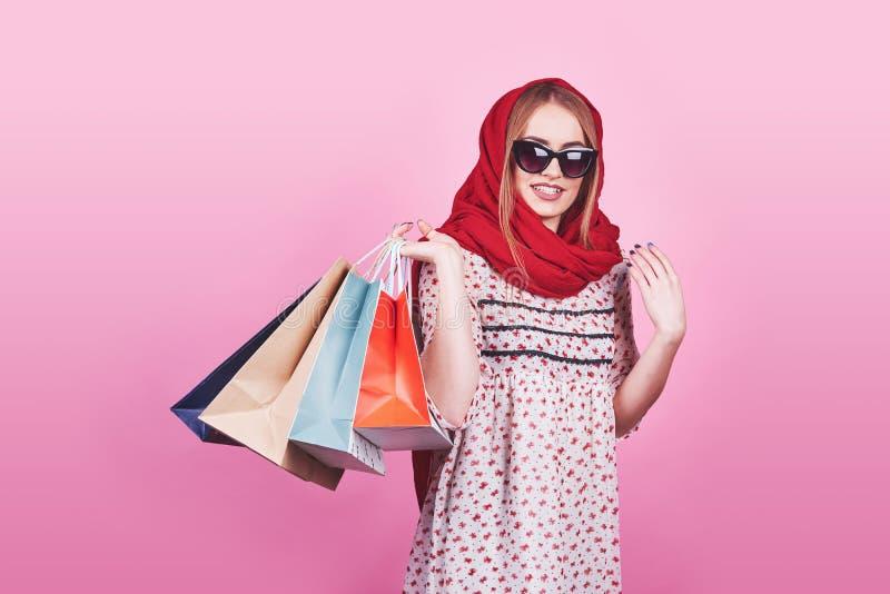 Portrait de jeune femme de sourire heureuse avec des paniers sur le fond rose photos stock