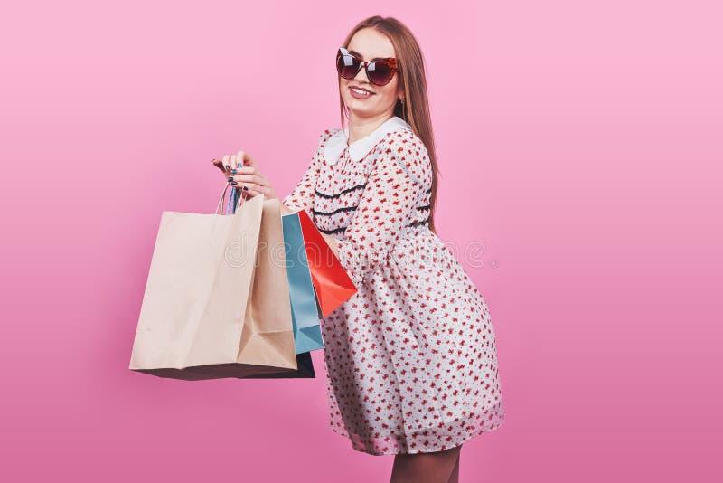 Portrait de jeune femme de sourire heureuse avec des paniers sur le fond rose image libre de droits