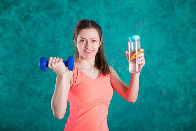 Portrait de jeune femme de sourire heureuse dans l'usage de forme physique avec la bouteille de l'eau et d'haltères, au-dessus de photo libre de droits