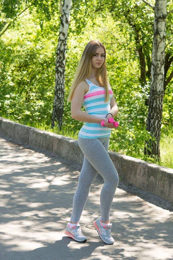 Portrait de jeune femme sportive avec des haltères au parc Femme dedans photos stock